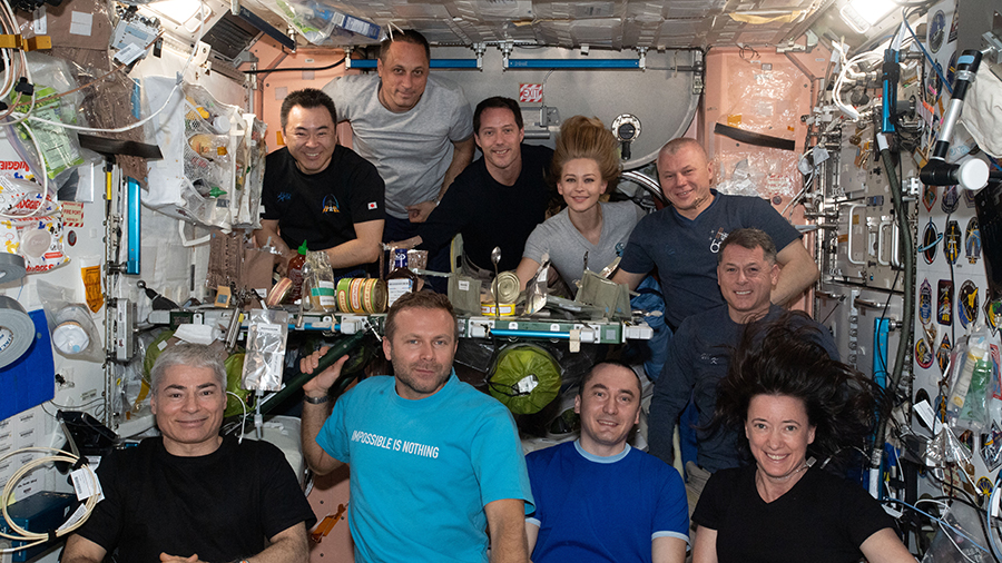 The ten station inhabitants are gathered together in the Unity module for a meal and a portrait. In the front row (from left) are, Mark Vande Hei, Klim Shipenko, Pyotr Dubrov, and Megan McArthur. In the back row (from left) are, Akihiko Hoshide, Anton Shkaplerov, Thomas Pesquet, Yulia Peresild, Oleg Novitskiy, and Shane Kimbrough.