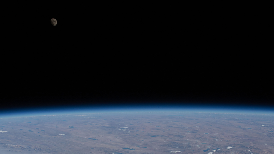 The waxing gibbous Moon is pictured from the space station over Earth's horizon.