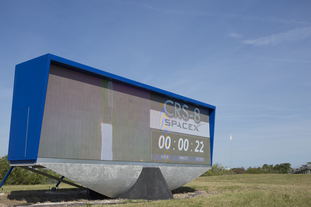 SpaceX Falcon 9 rocket lifts off behind the countdown clock