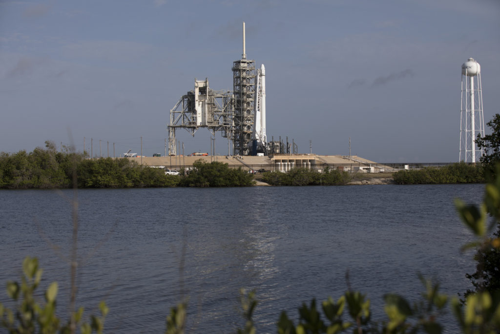 The SpaceX Falcon 9 rocket, topped by the Dragon spacecraft, awaits liftoff from Launch Complex 39A.