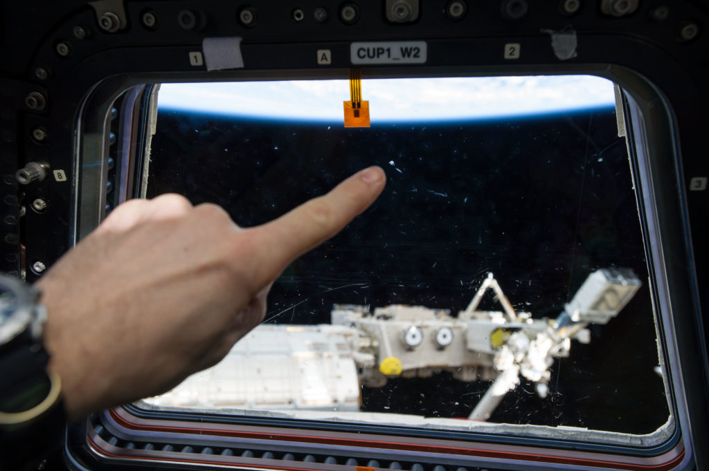 Photographic documentation of a Micro Meteor Orbital Debris strike one of the window's within the space station's Cupola.