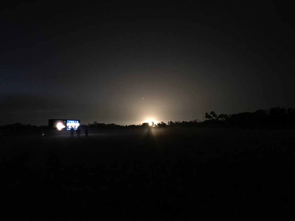 The glow of liftoff shines through the treeline southeast of the Launch Complex 39 news center at Kennedy Space Center.