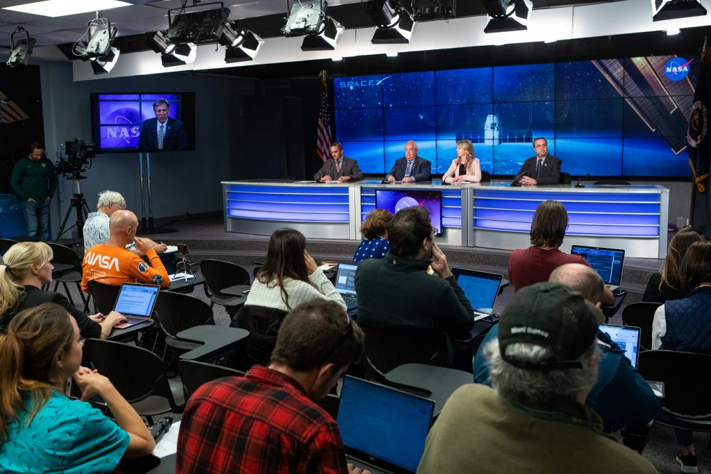 Dustin Cammack, NASA Communications, far left, moderates a prelaunch news conference on Dec. 3, 2019, for SpaceX's 19th Commercial Resupply Services (CRS-19) mission for NASA to the International Space Station, at the agency's Kennedy Space Center in Florida. Speaking to members fo the news media are, from left, Bryan Dansbury, assistant program scientist, International Space Station Program Science Office at NASA; Jessica Jensen, director, Dragon Mission Management at SpaceX; and Mike McAleenan, launch weather officer, U.S. Air Force 45th Space Wing.