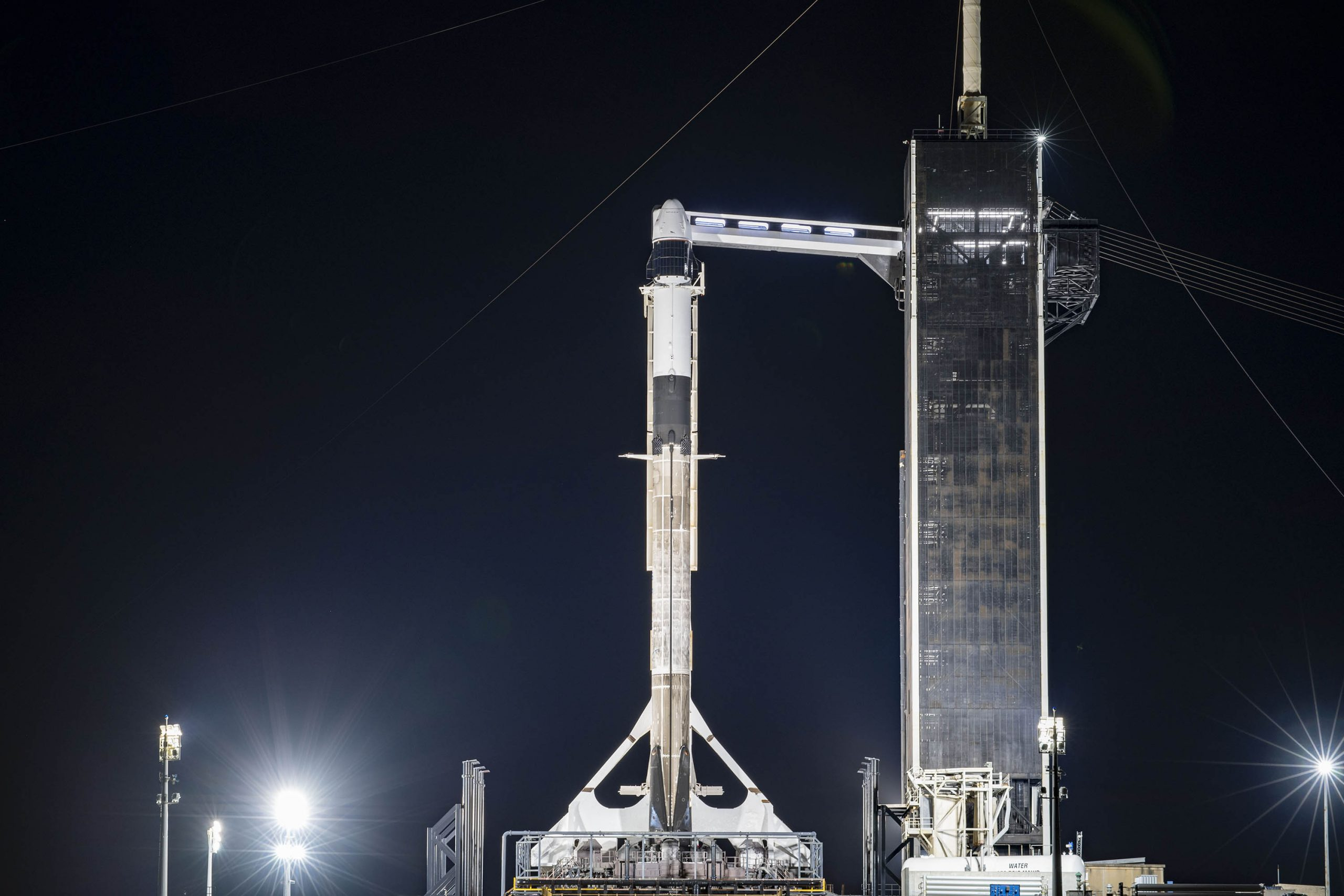 A SpaceX Falcon 9 rocket and Cargo Dragon spacecraft stand ready for liftoff for the company's CRS-21 launch.
