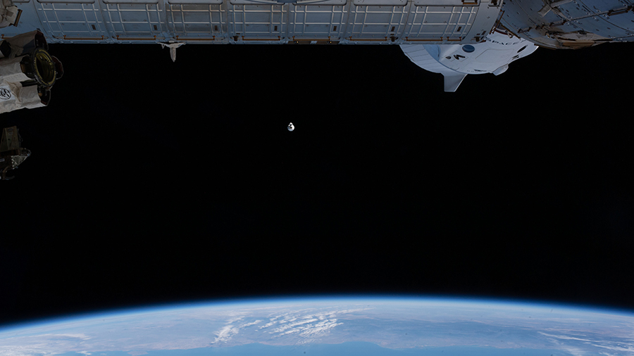 The upgraded SpaceX Cargo Dragon vehicle approaches the space station as both vehicles were orbiting above the Pacific Ocean off the coast of Mexico.