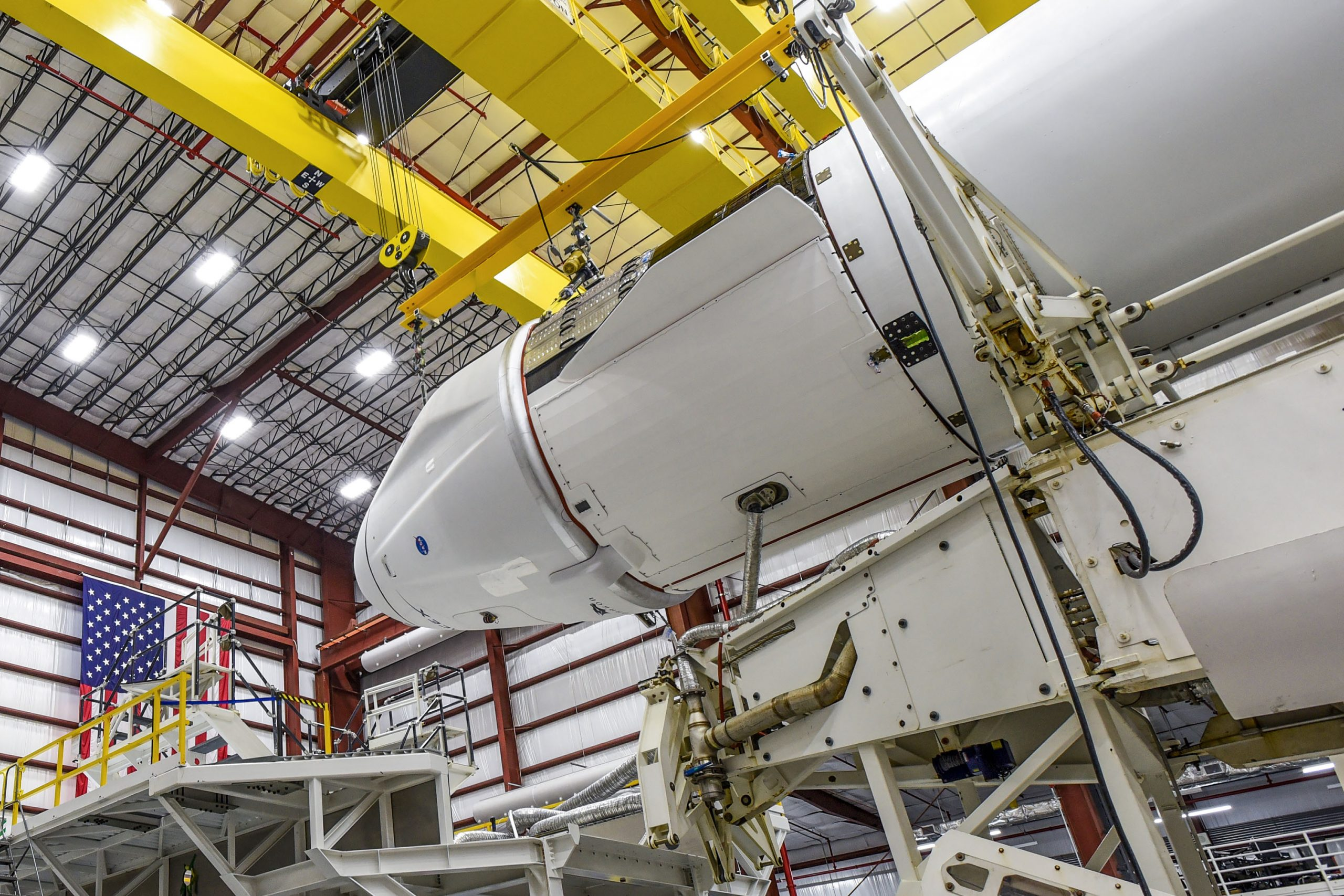The Dragon spacecraft and Falcon 9 rocket are seen inside the hangar at Kennedy Space Center in Florida.