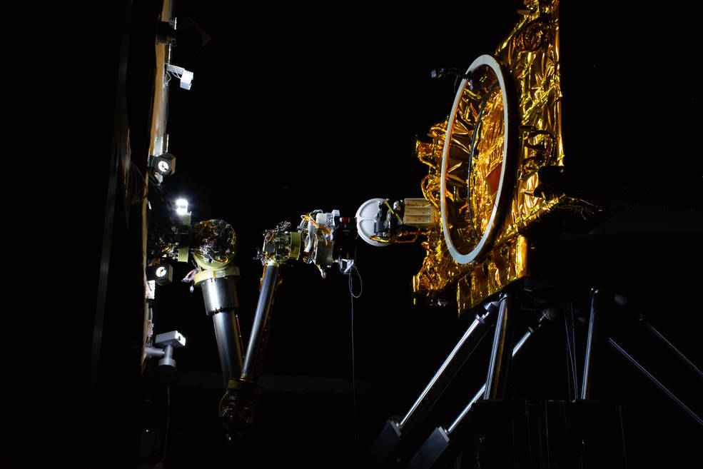 A six-legged, 10 by 16-foot robot mimics how satellites move in space. Sitting on top of the hexapod is a partial mockup of a satellite. Mounted to a panel close by, representing the payload deck of a robotic servicing spacecraft, is an advanced robotic arm.