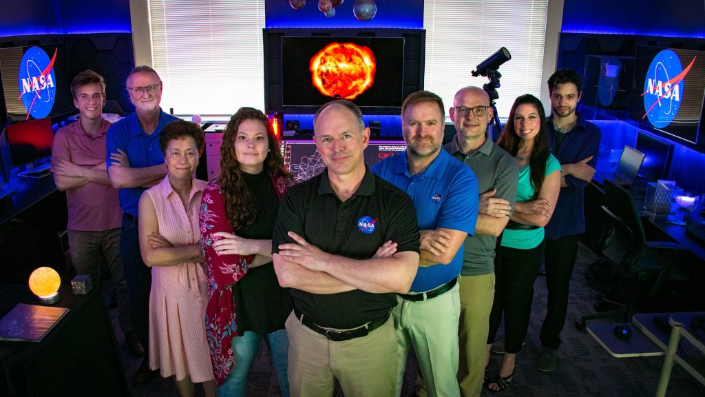 Members of the lab stand in a V-shape formation in the NASA STEAM Innovation Lab