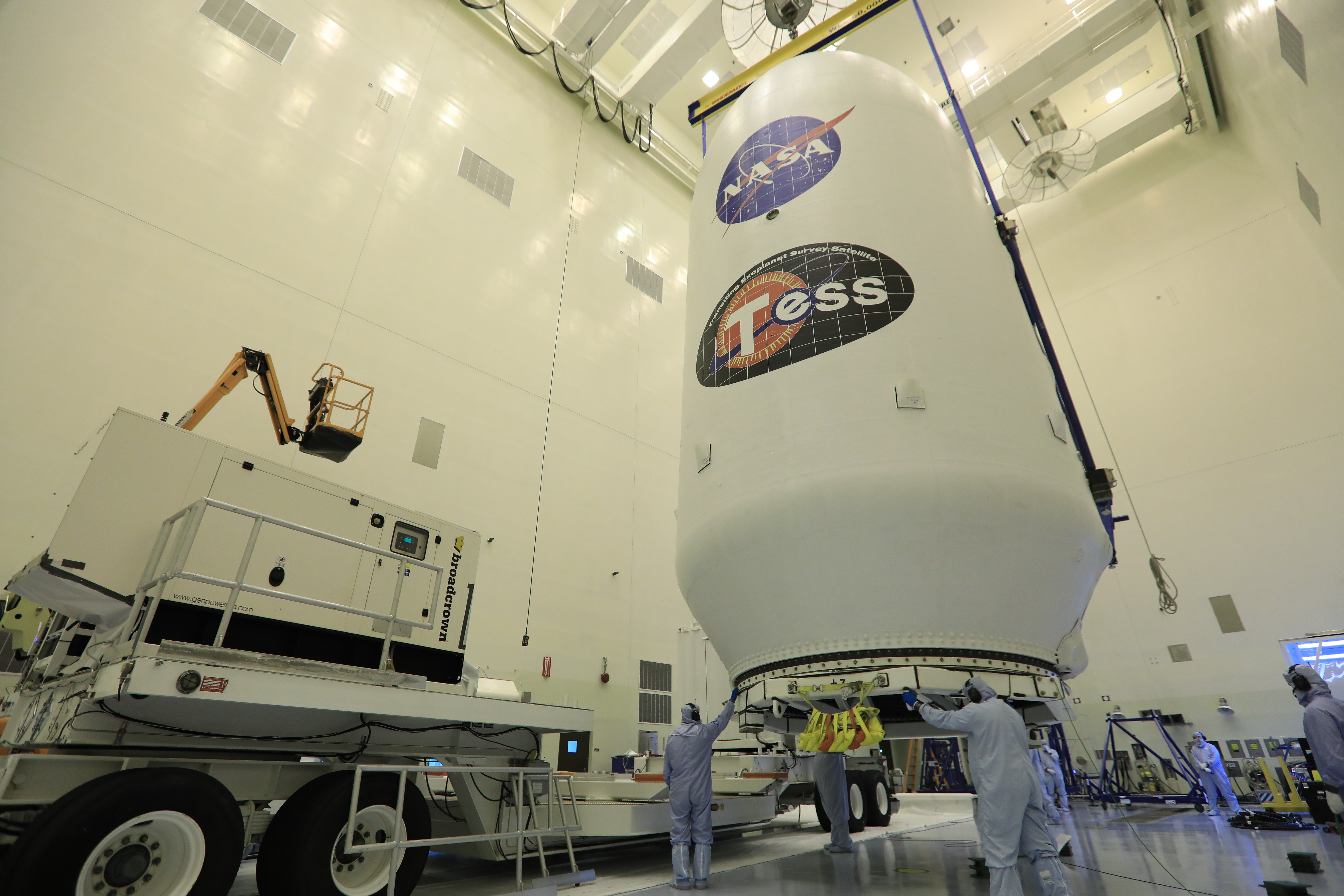 Inside the Payload Hazardous Servicing Facility at NASA's Kennedy Space Center in Florida, technicians assist as the SpaceX payload fairing containing the agency's Transiting Exoplanet Survey Satellite (TESS) is moved by crane to a transporter.