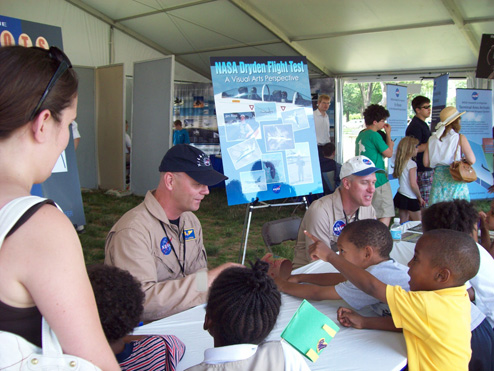 NASA pilots talk to the public at an air show exhibit.