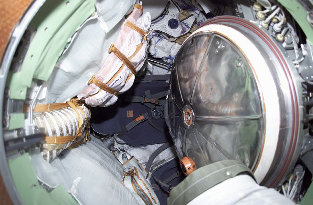 Interior view of Soyuz spacecraft with Sokol suits, hatch, and crew seats.