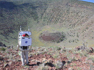 Astronaut Stan Love looking at crater