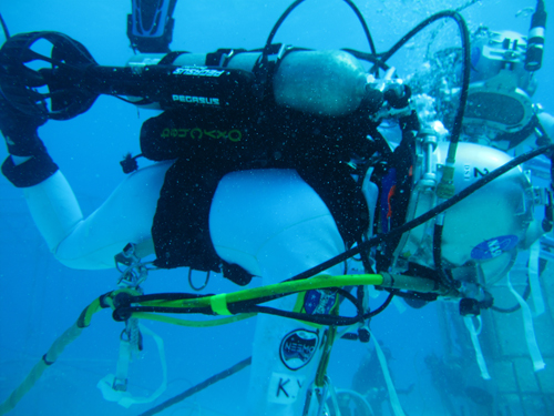 Aquanaut Kimiya Yui (JAXA) uses a jetpack while performing tasks underwater.