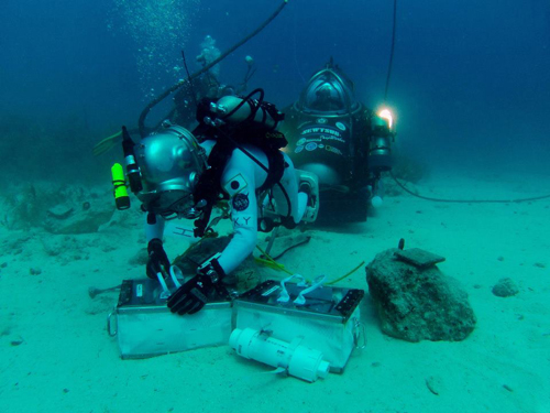 Photo of JAXA astronaut Kimya Yui collects chipping samples from a rock simulating an asteroid boulder.