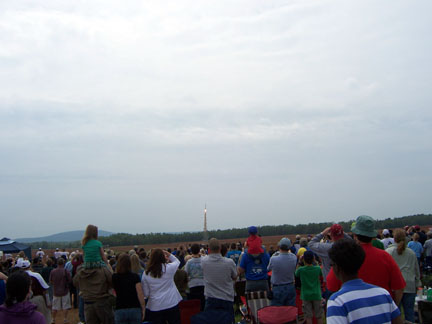 A crowd of people watching a rocket launch