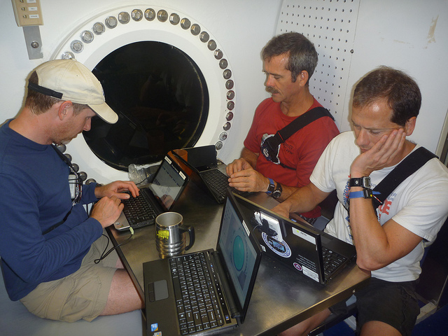 The NEEMO crew sitting at a table working on laptop computers