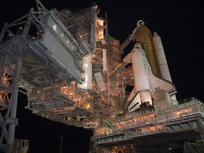 Space shuttle Discovery on the pad at night awaiting launch