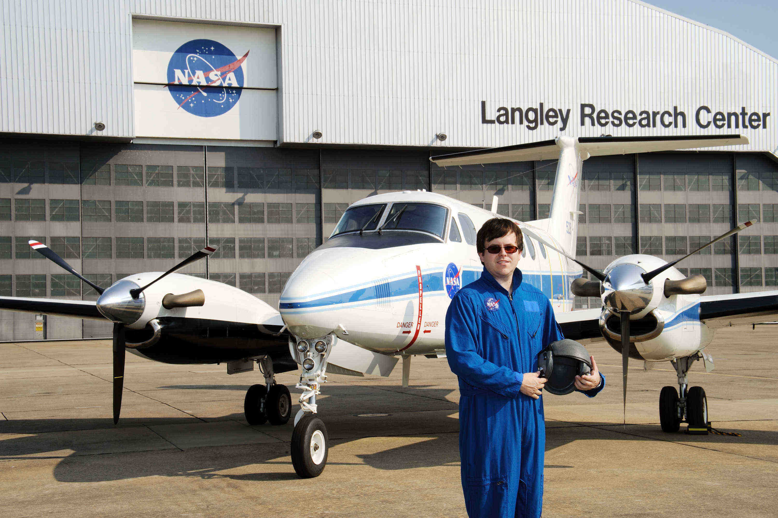 Stephen Pace in front of a NASA aircraft and hangar