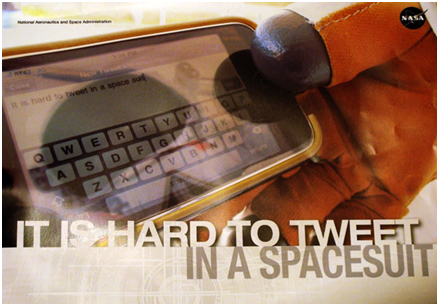 A poster showing a gloved hand holding a smart phone with the words 'It is hard to tweet in a spacesuit'