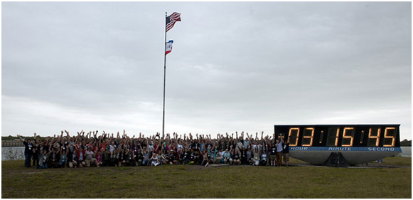 A large group of people stand next to a large clock