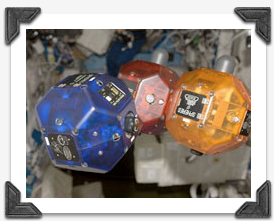 Close-up view of three bowling-ball-sized free-flying satellites called Synchronized Position Hold, Engage, Reorient, Experimental Satellites (SPHERES) in the Destiny laboratory of the ISS.