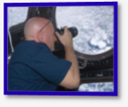 NASA astronaut Scott Kelly, Expedition 26 commander, uses a still camera to photograph the topography of a point on Earth from a window in the Cupola of the International Space Station.