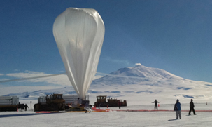 The balloon, ready to launch, dwarfs launch crew standing on the ice field.