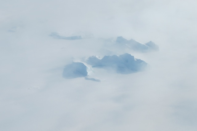 Icebergs in a northwest Greenland fjord shrouded in fog.