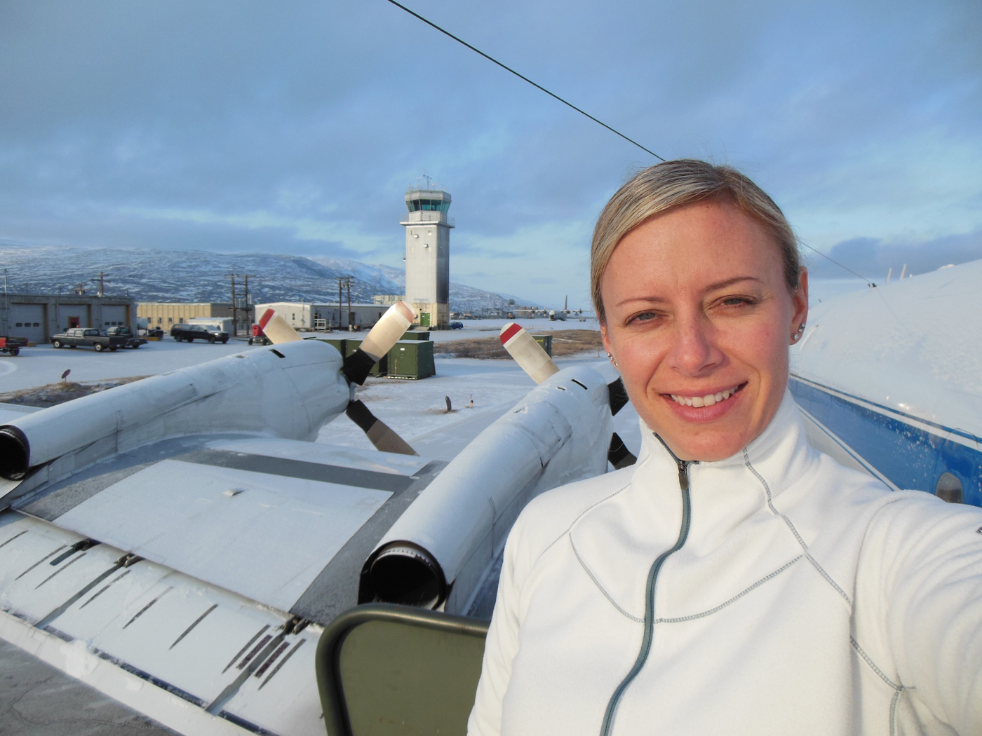 Christy Hansen in Kanger, Greenland, after one of Operation IceBridge's science flights. Behind her is the air traffic control tower, as well as the P-3B propellers.