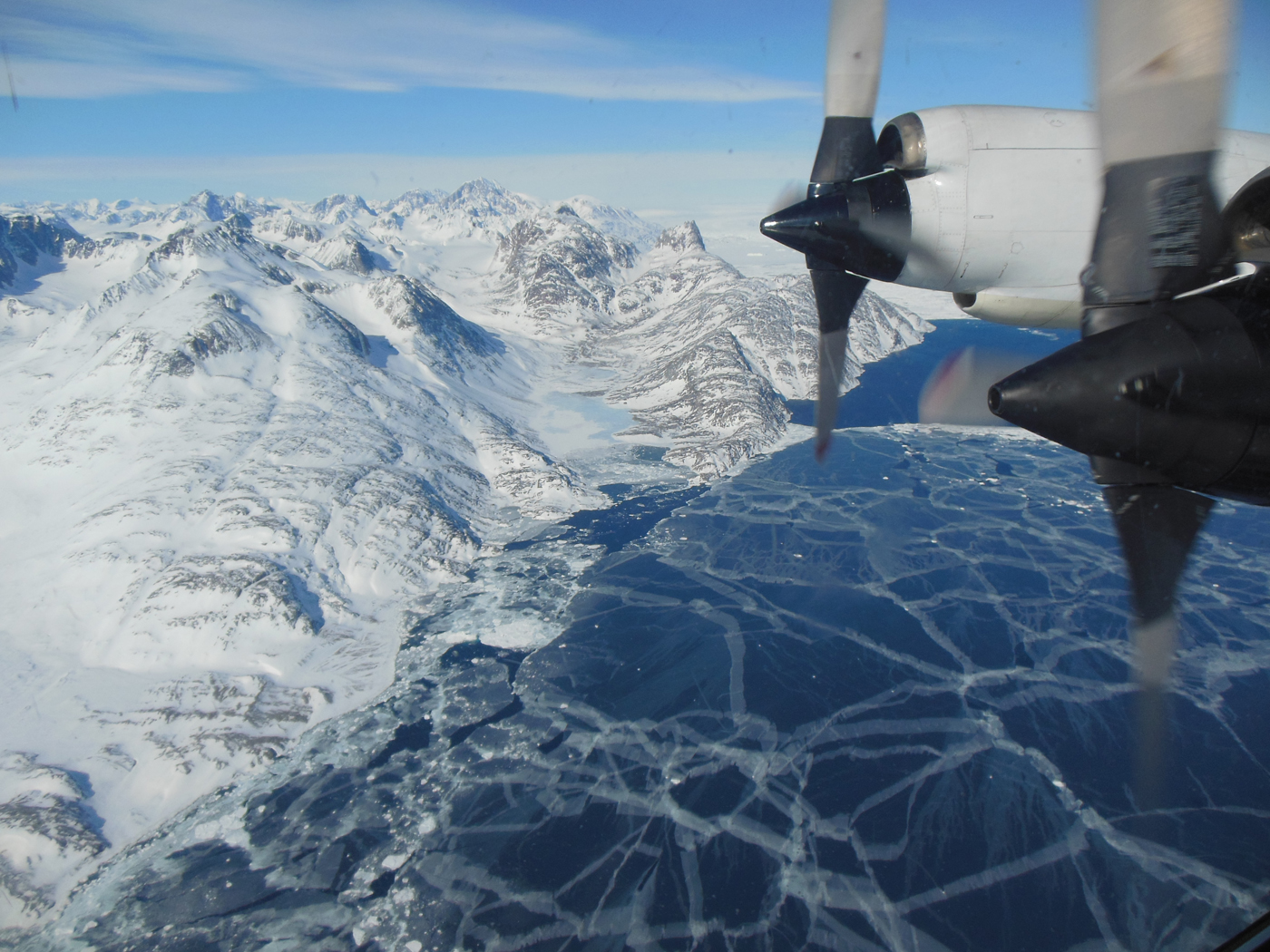The plane flies over sea ice. The P-3B propeller can be seen out the window of the plane.