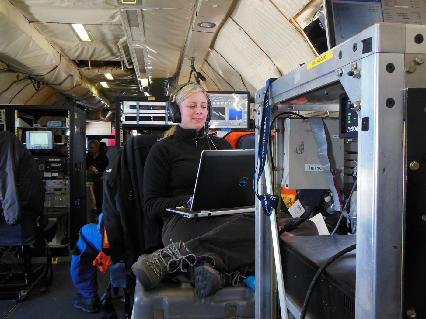Christy Hansen sits on a toolbox while she working on the Operation IceBridge flight. She is surrounded by various scientific instruments.