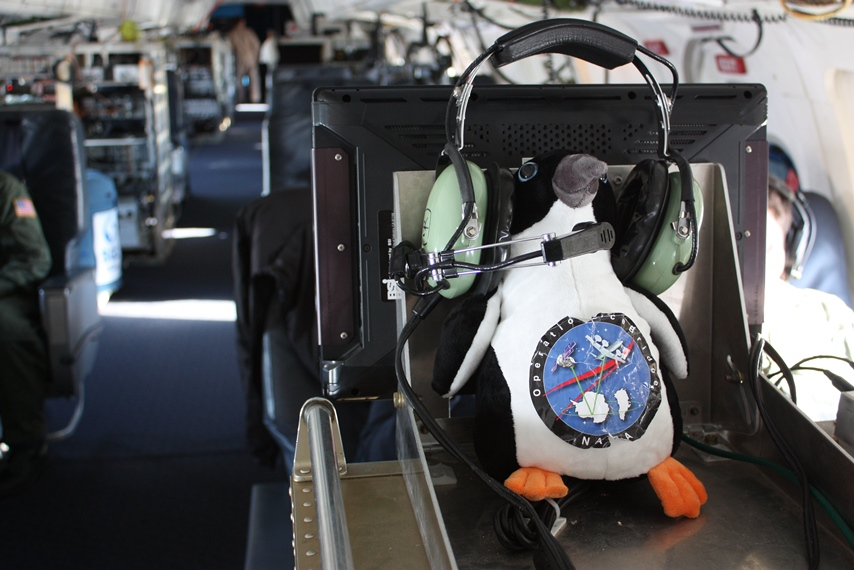 The IceBridge penguin mascot using the DC-8's satellite phone headset.
