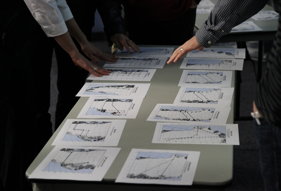 Science team members sort through printed copies of proposed flight lines.
