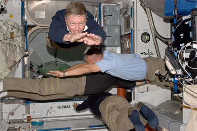 Four crew members float through the space station in four different directions.