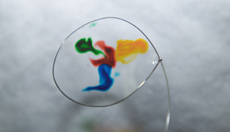 Water with drops of color suspended in a wire loop