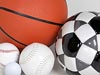 Basketball, soccer ball, softball, baseball and golf ball grouped on a white surface