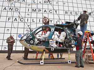 NASA technicians prepare to test a MD-500 helicopter with four crash test dummies inside