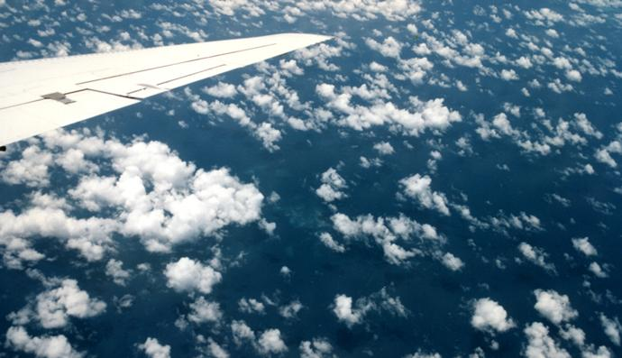 Puffy fair weather cumulus clouds and hints of reefs are visible below the right wing of NASA's DC-8. Credit: NOAA Photo Library/Dr. Joanne Simpson ...